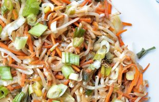 Stir-fried mung beans, carrots, cabbage, and green onions on a white serving platter with a large, metal serving spoon.