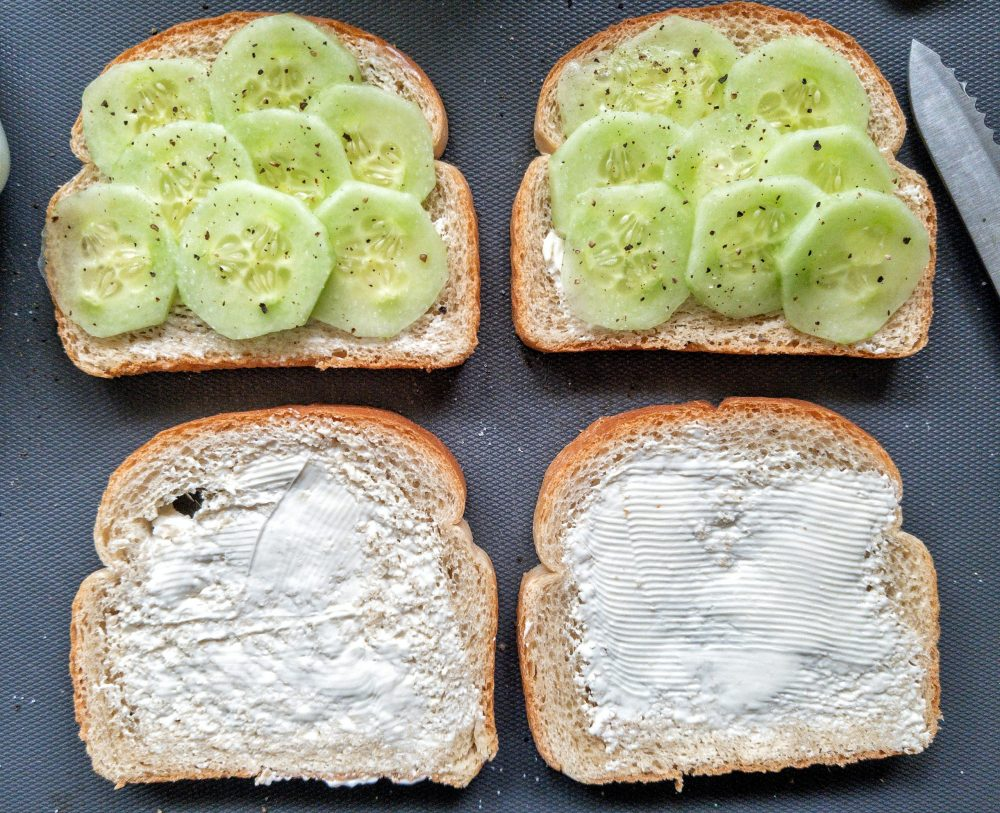 Four slices of buttered, white bread. Two slices with sliced cucumber, salt, and ground black pepper