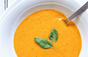 Blended and smooth roasted tomato basil soup in a white bowl garnished with two basil leaves