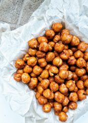 Roasted chickpeas tossed with smoked paprika and salt in a small dish lined with parchment paper