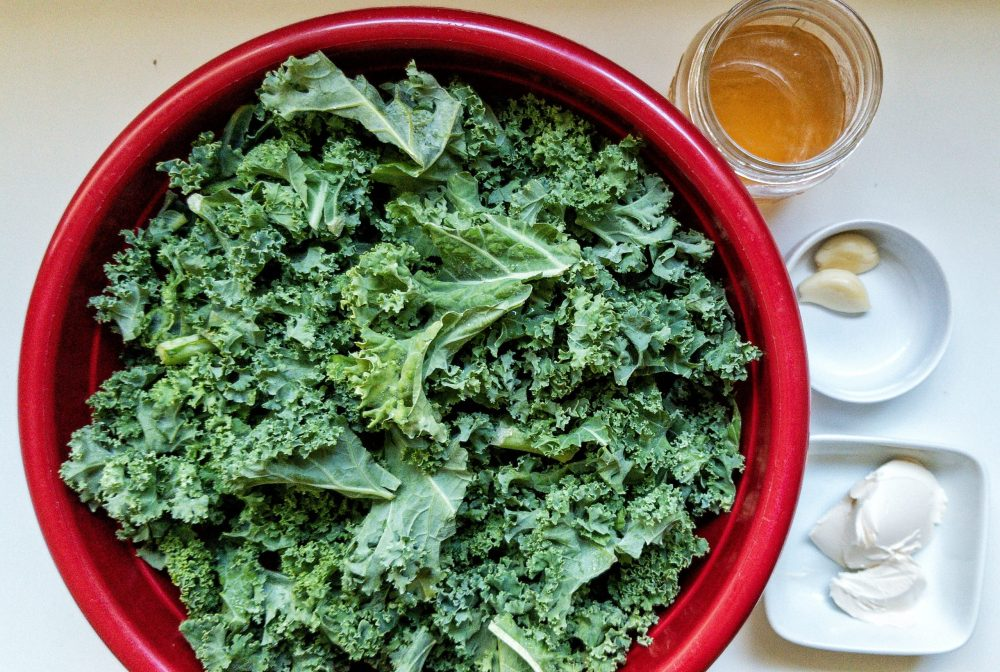 A bunch of raw kale in a large mixing bowl with measured vegan butter, garlic, and vegetable stock