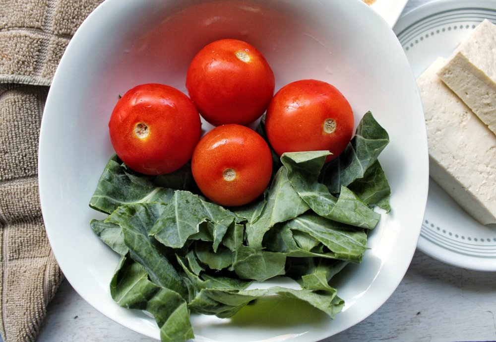 Collard greens and tomatoes in a white bowl