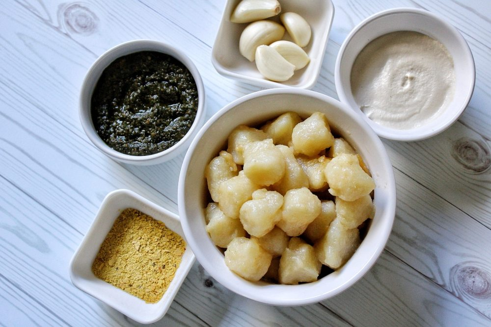 Gnocchi, cashew sauce, garlic, pesto, and nutritional yeast in small bowls
