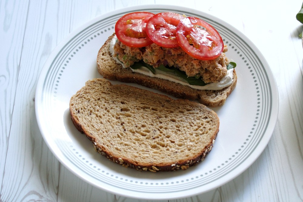 Open face chickpea salad sandwich on a plate topped with sliced tomatotes