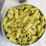 Rigatoni pasta in a creamy avocado sauce in a gray bowl. Topped with chili flakes.