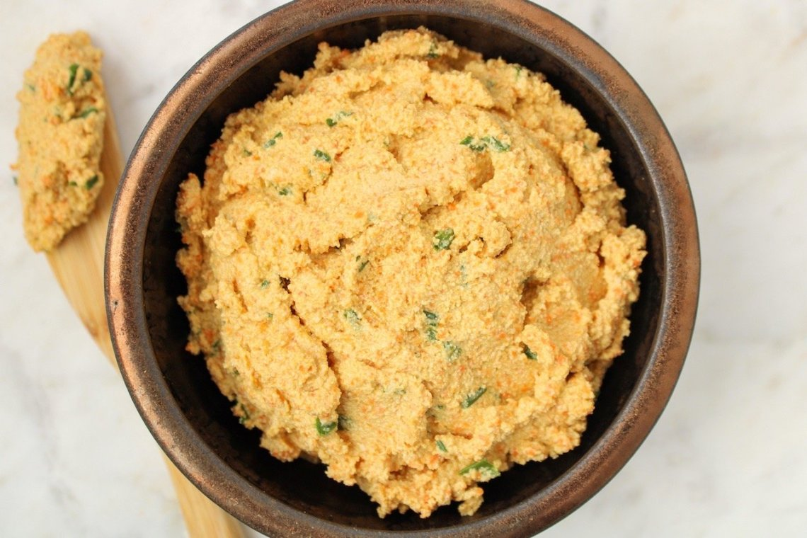 Homemade tofu spread (orange color dip with chopped chives inside) in a dark small bowl. On the side of the bowl, there is a wooden butter knife with some of the dip spread on it.