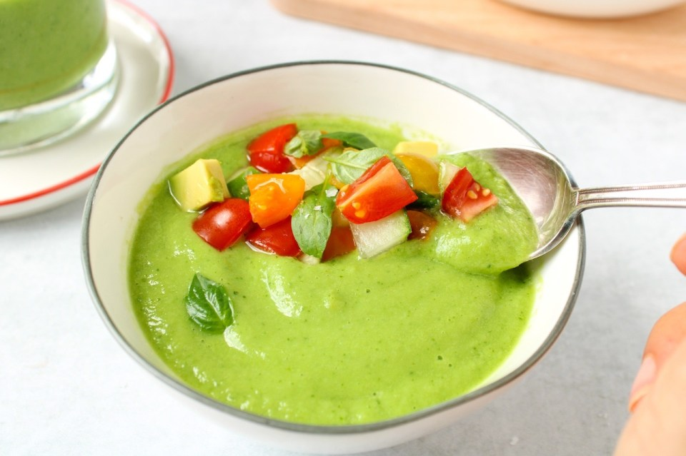 There is a spoon grabbing some of the green chilled soup that is in a small white bowl. The soup is topped with chopped cucumber, avocado and cherry tomatoes.