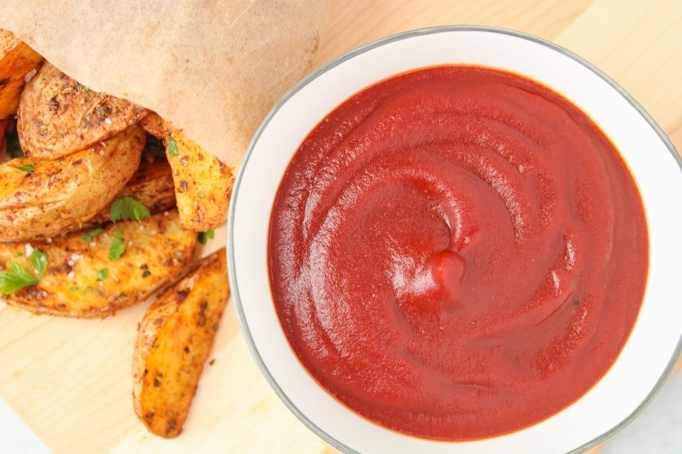 A few pieces of roasted potato are lying beside a white bowl containing homemade BBQ ketchup