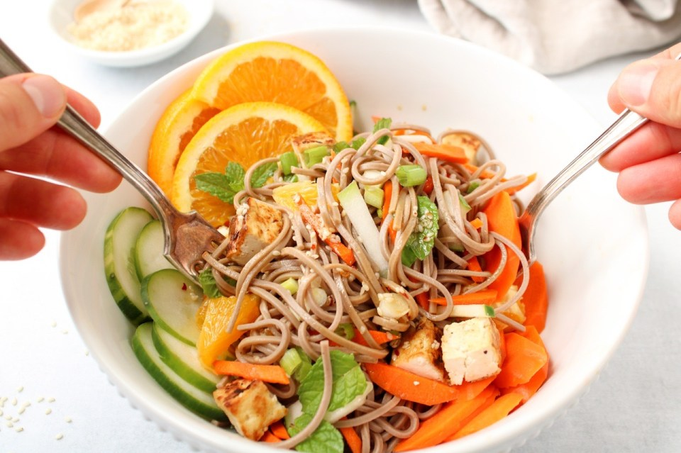 Two hands are holding a fork each and mixing a mixture of soba noodles with vegetables and oranges.