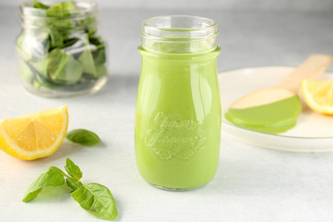 Displayed is a glass container containing a creamy green sauce. On the side, there are sliced lemon, a bowl with spinach leaves and a spoon covered with the sauce.