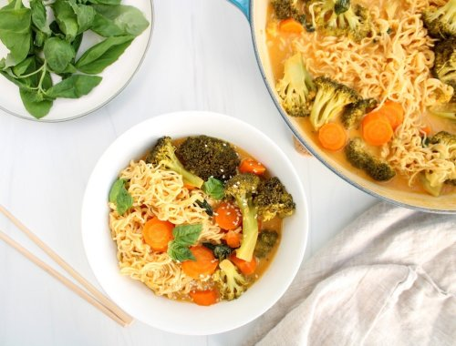 There is a white bowl containing a one-pot broccoli ramen topped with sesame seeds and fresh basil. On the side, you can see a portion of the large pot where the curry cooked in, a small plate with more fresh basil, a beige hand towel and 2 chop sticks.