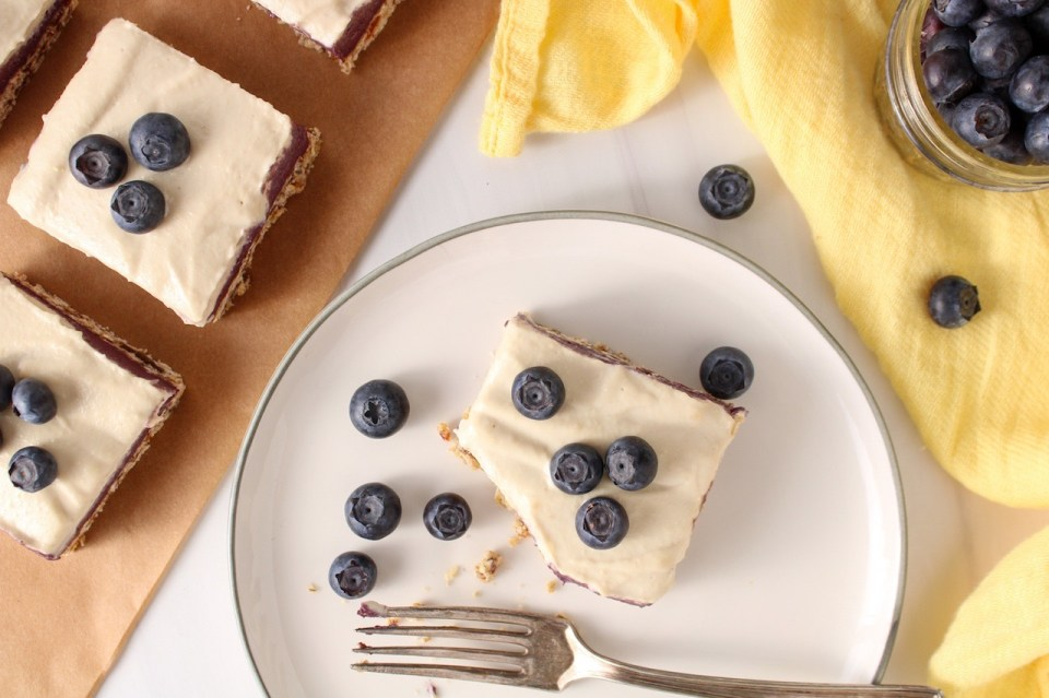 There are a few squares of vegan blueberry cheesecake on a piece of parchment paper with a piece of the cake on a white plate and topped with fresh blueberries. A bite was taken from the piece on the plate and the plate is surrounded by a yellow hand towel and a small glass container with fresh blueberries.
