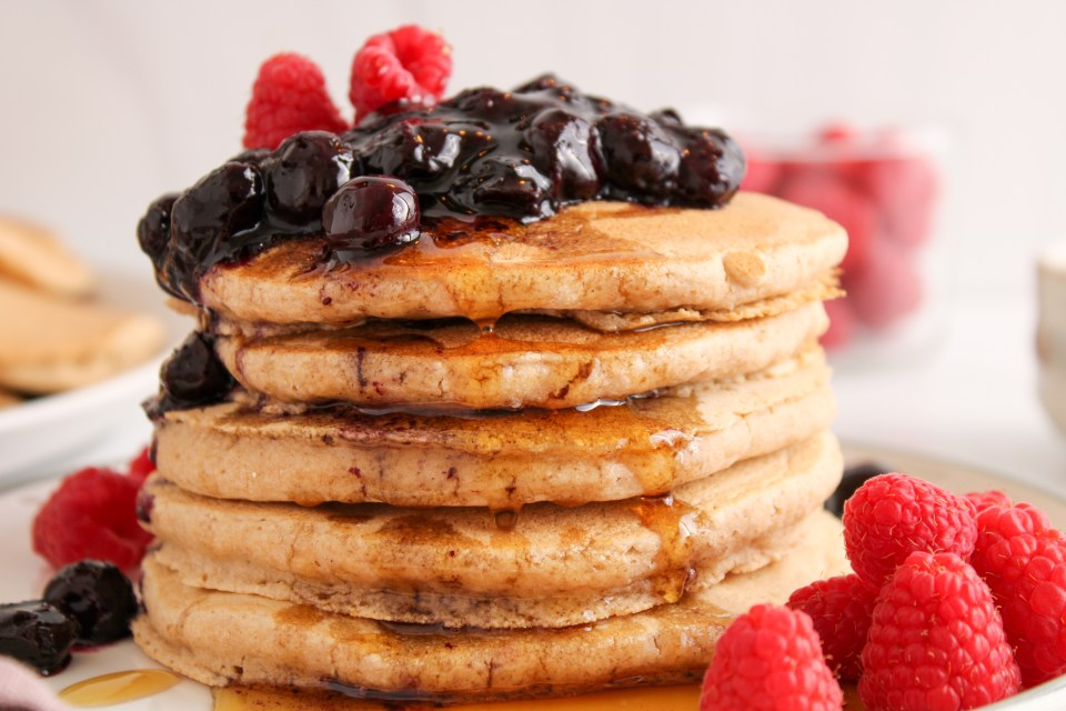 There are 5 oat flour pancakes stacked on top of each other on a white plates. There is a quick blueberry jam on top with some fresh raspberries. Also on the side, there is a glass jar with fresh raspberries and a large white plate with more of the pancakes.