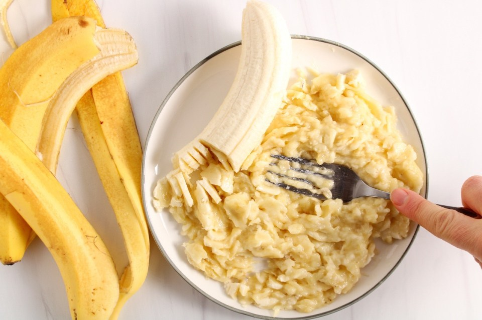 There is a hand holding a fork and mashing bananas on a white plate. There are banana peels on the side of the plate.