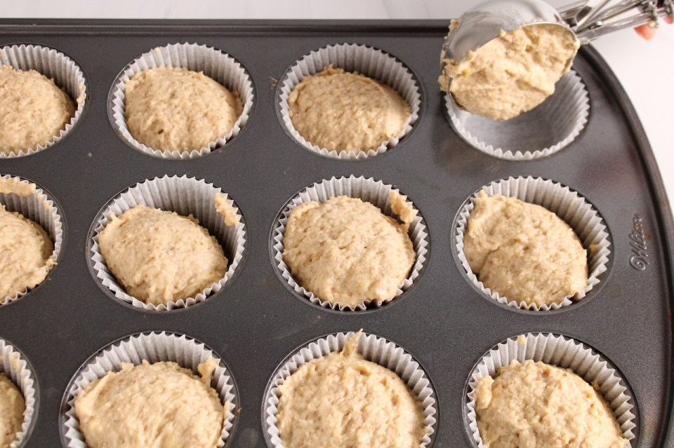 Showing is a regular muffin pan with white paper liners being filled with a muffin batter using a ice cream scoop.