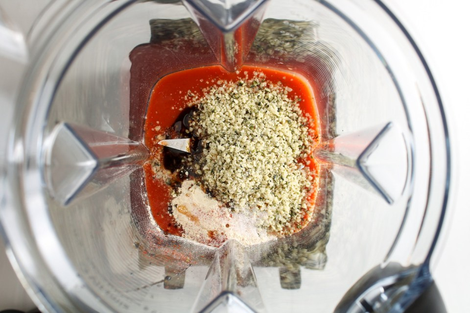 Close up of a few ingredients at the bottom of a blender just about to be blended (to prepare a creamy hot sauce)