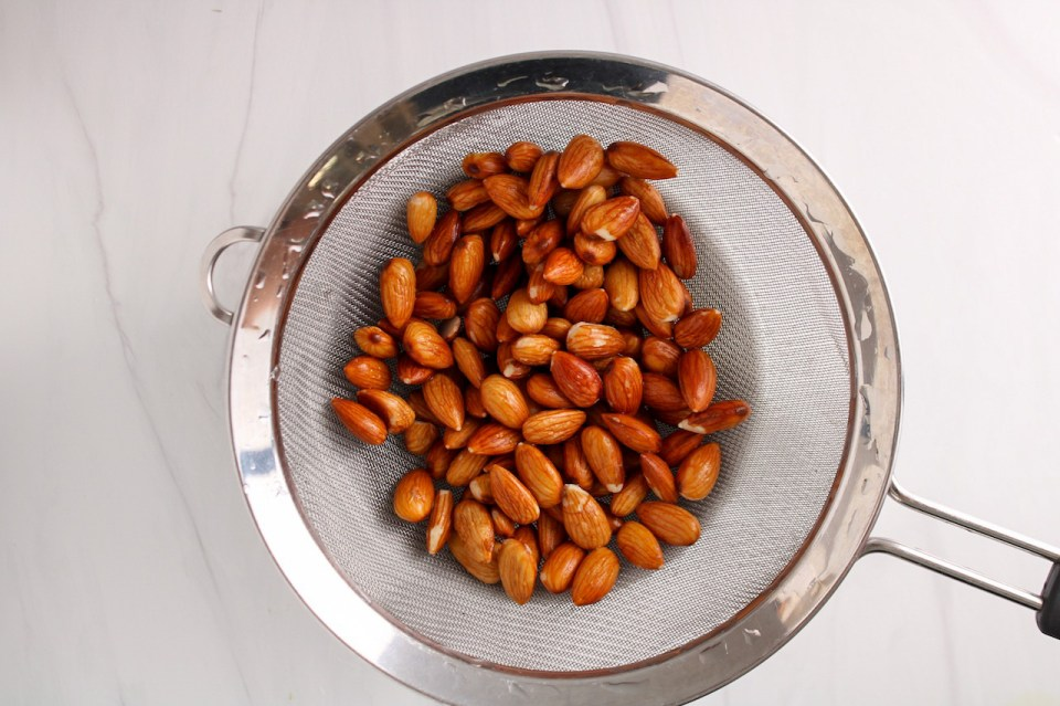 A handfull of raw almonds that were soaking in water are being drained in a fine mesh colander.