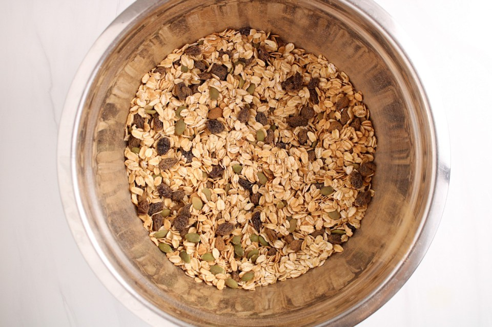 Showing is inside a stainless steel bowl containing a dry mixture of oats, raisin, pumpkin seeds and cinnamon.