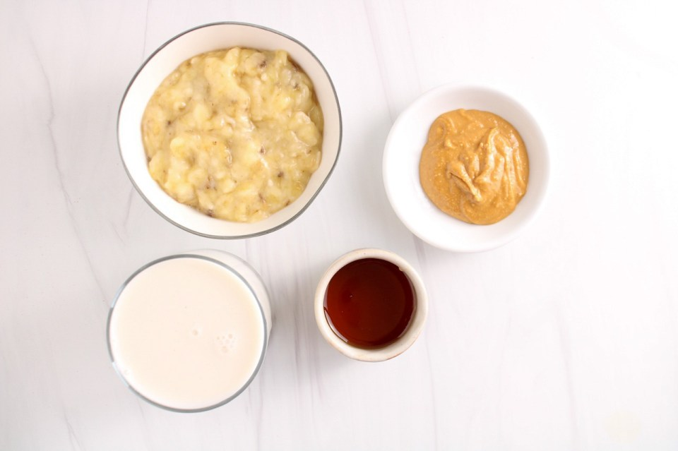 Showing are 4 bowls containing mashed bananas, maple syrup, vegan milk and peanut butter