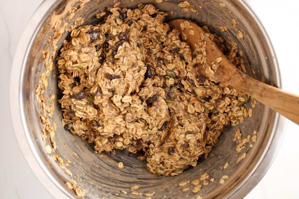 Showing is inside a stainless steel bowl containing a creamy oat mixture with a large wooden spoon stirring.