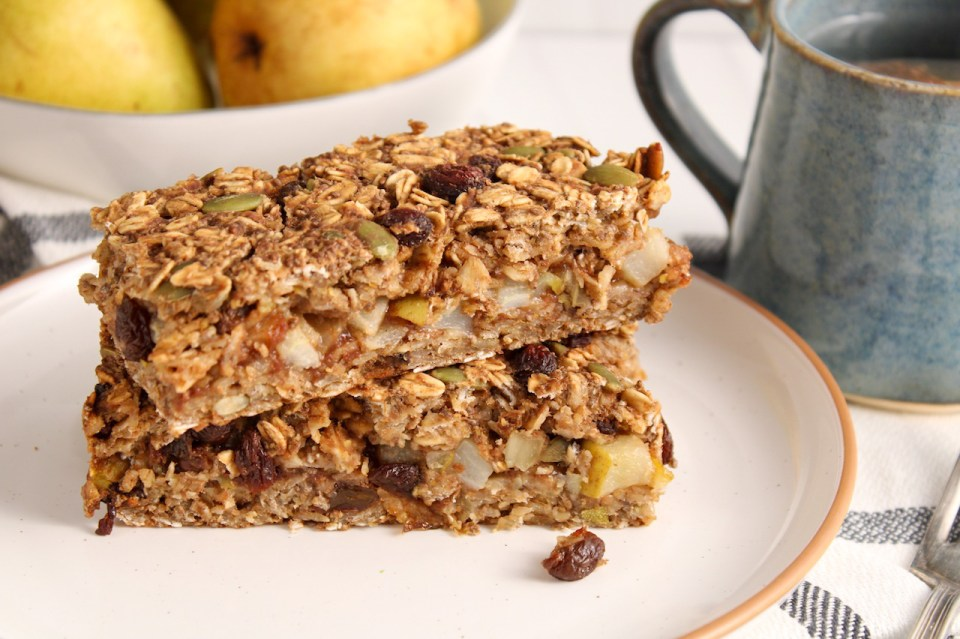 There are 2 oatmeal raisin bars on top of each other on a white plate. The plate is placed over a hand towel and there are a few pears and a cup of tea on the side.