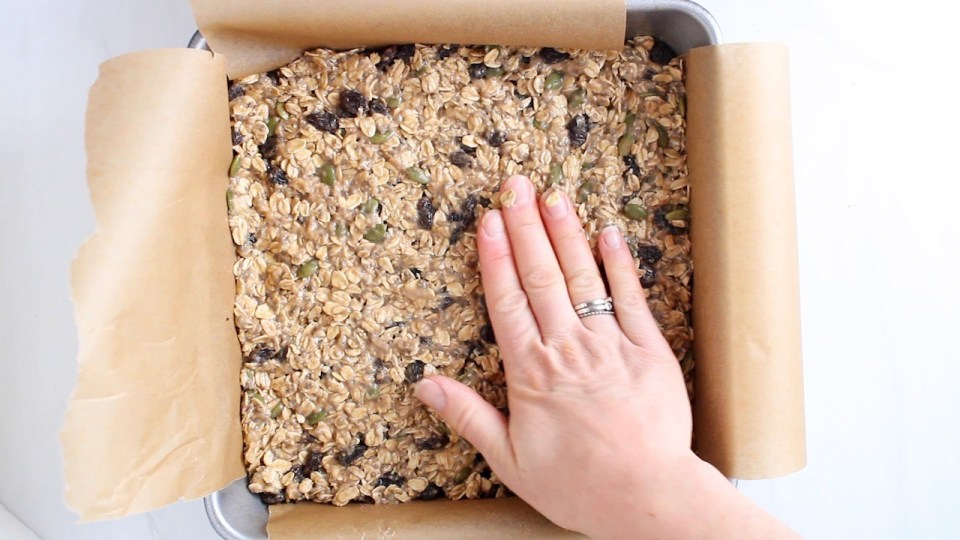 There is a hand pressing over a oatmeal mixture in a square cake pan.