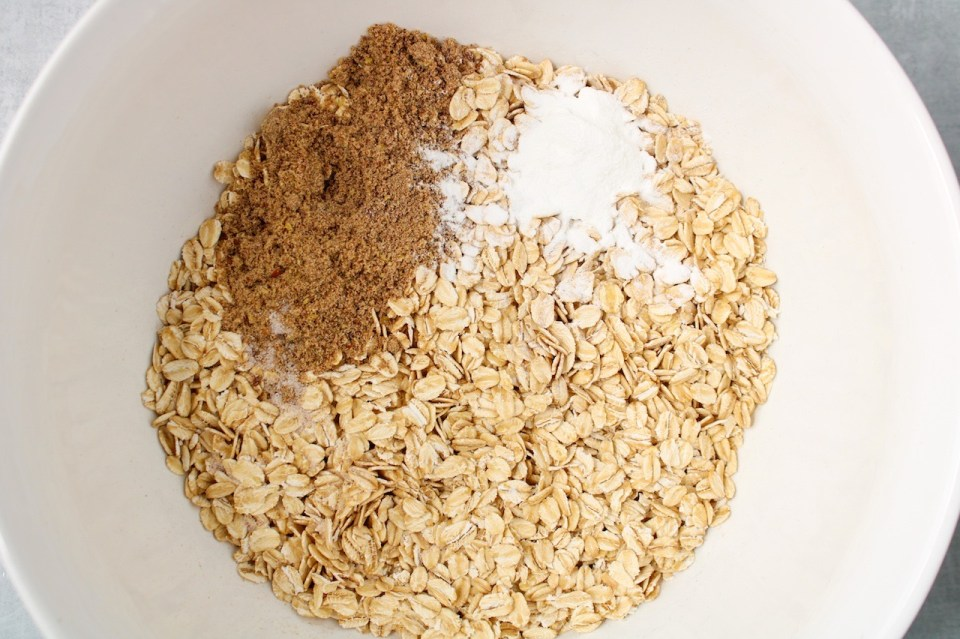 There are raw oats, flax seeds, baking powder and salt in a large white bowl.