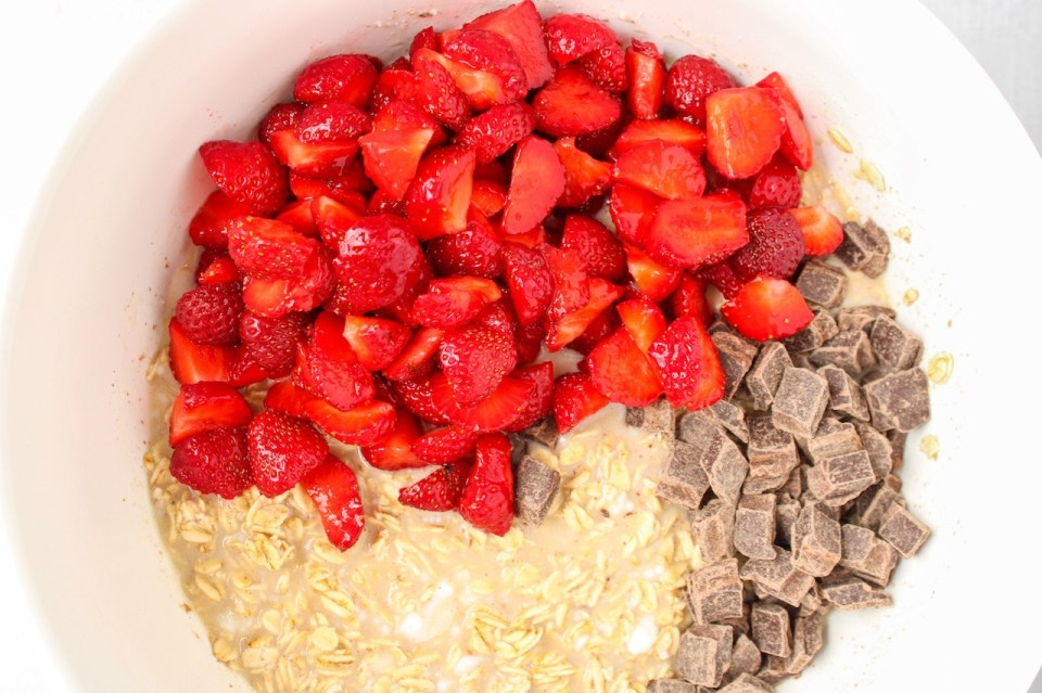 There is a wet oat mixture topped with diced strawberries and chocolate chips in a large white bowl.