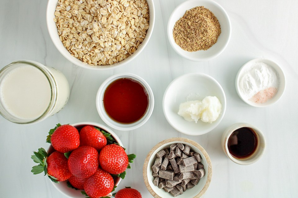 Displayed are the ingredients needed to make this recipe: fresh strawberries, raw oats, vegan milk, maple syrup, coconut oil, vanilla extract, salt, baking powder and dark chocolate chips.