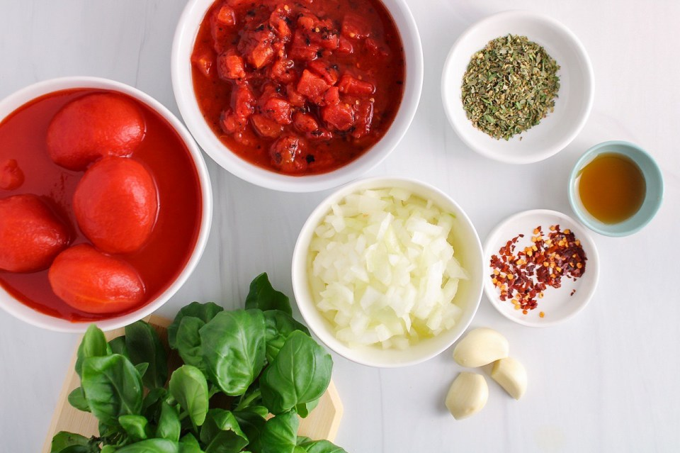 Ingredients needed to make a tomato sauce (canned tomatoes, onion, basil, dried herbs, red pepper flakes, garlic and maple syrup)
