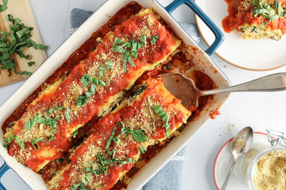 There are vegan lasagna roll-ups in a blue baking dish with plates and forks on the side as well as vegan parmesan cheese and chopped fresh basil. There is also a large spoon grabbing a roll-ups from the baking dish.