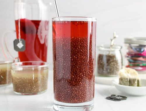 There is a see through tall glass containing a red fruity tea with chia seeds inside (chia seed tea). In the background, there is a large container with more tea, 2 small glasses with pale chia seed tea, a jar with chia seeds, a container with tea bags and a shallow small white bowl with the tea bags that were used to make the tea.
