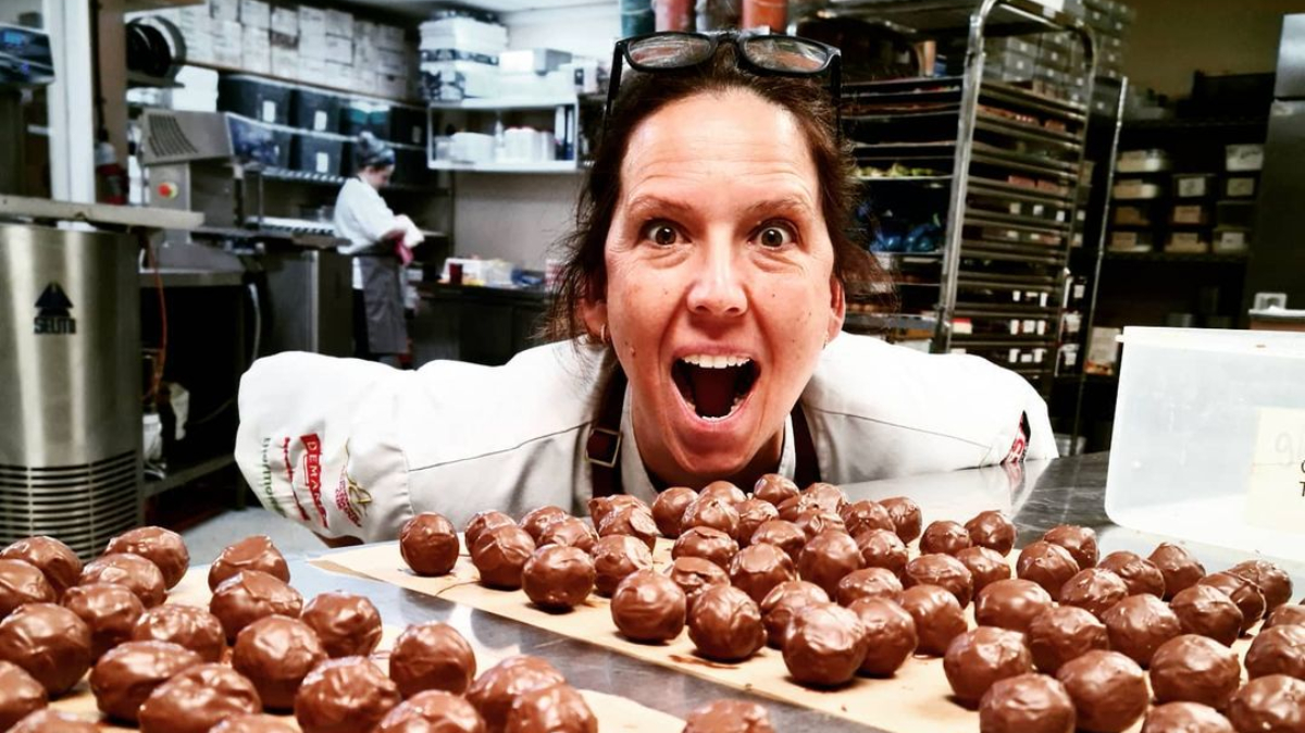 Chocolatier Ruth Hinks poses in a kitchen with chocolate