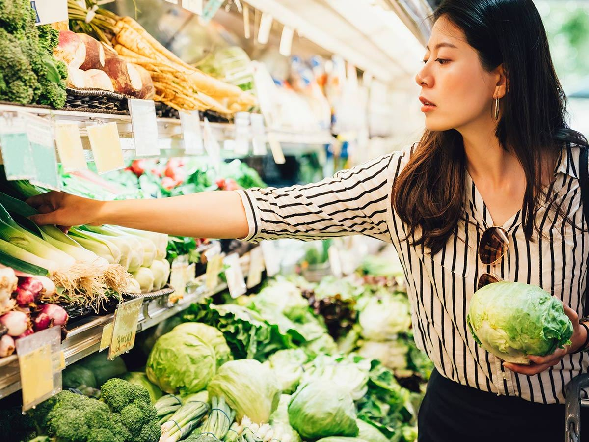 A young asian woman reaches for some vegetables in a supermarket. She is holding a lettuce.