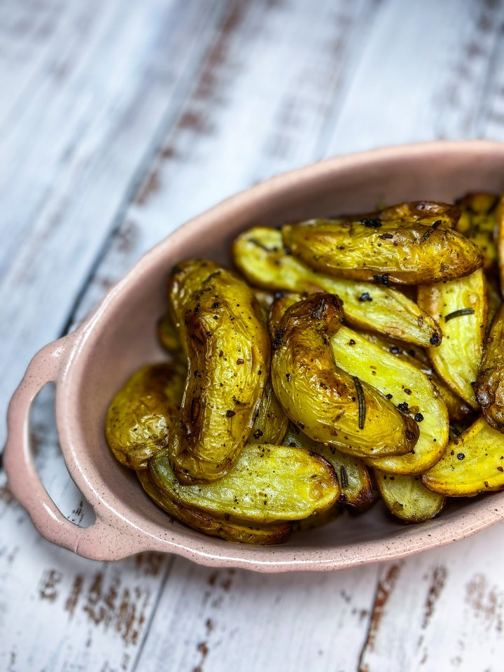 Fingerling potatoes in a baking dish topped with rosemary.