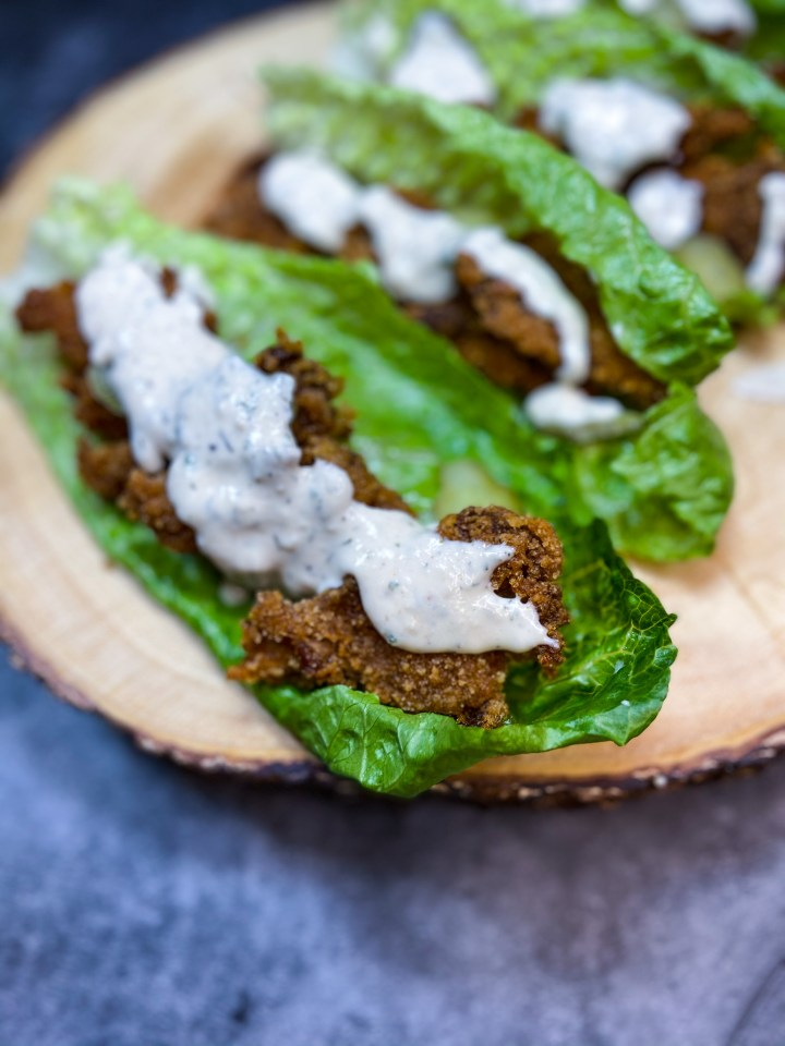 Fried oyster mushrooms in place of chicken in these vegan southern fried chicken wraps with vegan ranch sauce on top.