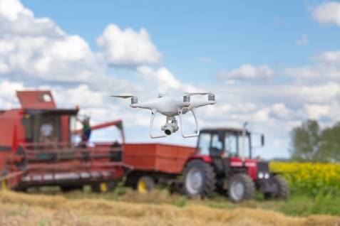 Camera drone in front of tractor and combine harvester in field