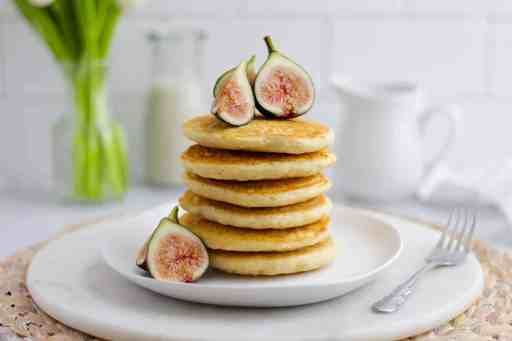 Stack of vegan pancakes on a white plate, garnished with freshly sliced figs
