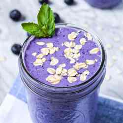 Picture of a purple smoothie in a mason jar. Topped with uncooked oats and a green sprig of mint.