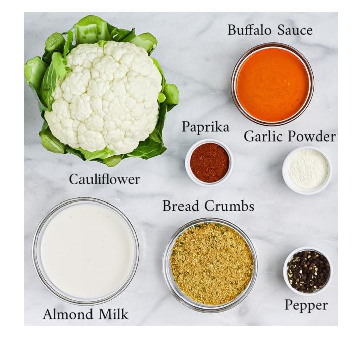 A head of cauliflower and circular containers each containing buffalo sauce, garlic powder, almond milk, paprika, breadcrumbs, and pepper.