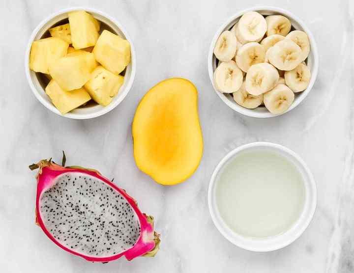 Smoothie ingredients, half a sliced dragon fruit, half a sliced mango, bowl of sliced bananas, bowl of sliced pineapple, bowl of coconut water.