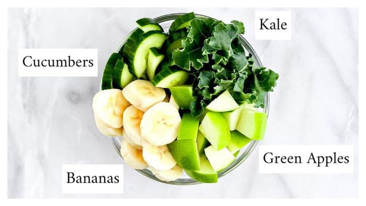 Picture of a glass bowl filled with kale, cucumbers, banana slices, and a chopped green apple.