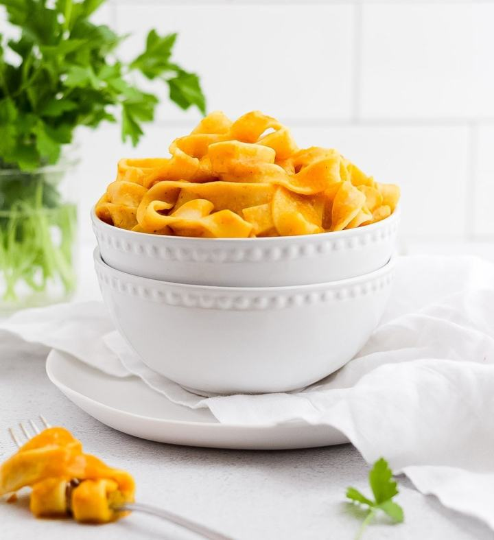 White bowl filled with pumpkin pasta with parsley garnishing on the side