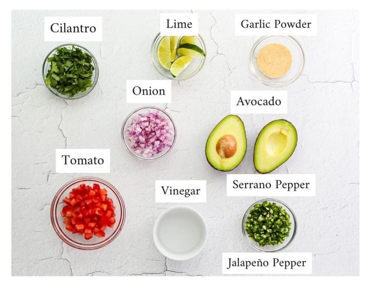 Picture of labeled ingredients within small bowls, including: cilantro, lime wedges, garlic powder, red onion, a sliced avocado, tomato, white vinegar, and a bowl on finely chopped serrano and jalapeno peppers.