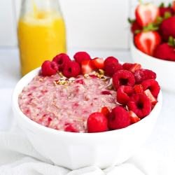 A Picture of pink raspberry oats in a white bowl, garnished with fresh berries and granola.