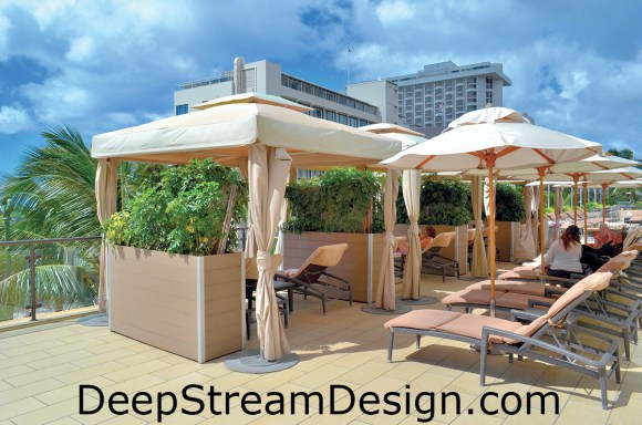 42 inch high tall commercial wood planters in recycled plastic lumber feature casters for mobility, allowing privacy between massage tables on the pool terrace of a Waikiki waterfront hotel.