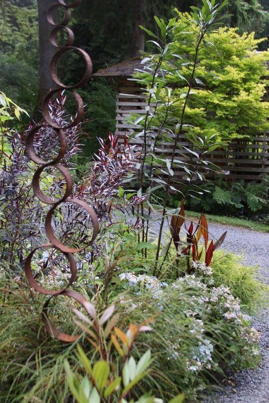 welded pipe sculpture in garden setting