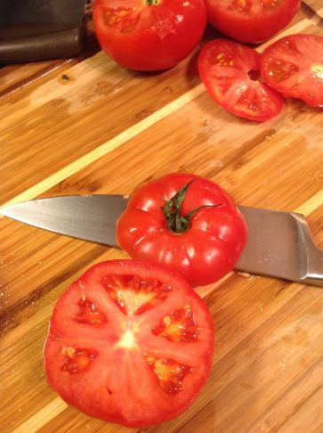 Slice off the tops of the tomatoes about 1/2-inch from the top. Keep the tops for an elegant presentation