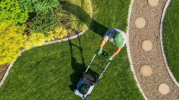 person mowing a beautiful yard that includes all landscape design principles