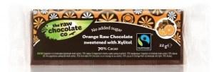 """Ciocolata Raw cu Portocale, Indulcita cu Xilitol 22g Doresti sa mananci ciocolata, insa fara zahar? Ia-ta ca se poate: un gust intens de ciocolata neagra cu note delicioase de portocala. Noi folosim xylitol de la arborii maturi de mesteacan. Xylitolul este un indulcitor provenit din maduva arborilor de mesteacan din Finlanda. Numele provenind de la cuvantul grecesc """"xylos"""" care inseamna copac si """"tol"""" care inseamna indulcitor. Ingrediente: cacao, xylitol, unt de cacao virgin,ulei de portocala, urme de nuci, produs in UK. Ciocolata noastra este vagana, fara zahara si fara soia. Deasemenea nu contine alte ingrediente ce nu ar trebuie sa existe. Acest produs este 100% natural! Are proprietati extraordinare, te face pur si simplu sa zambesti si sa te simti minunat! Untul de cacao pe care il contine este standardizat si organic, ceea ce este foarte important pentru noi cat tu sa te bucuri de o ciocolata Raw, organica si de inalta calitate. Ne-am petrecut mult timp in a gasi cele mai bune ingrediente si in a obtine cea mai buna reteta pentru tine. Asta ne ajuta sa-ti oferim cea mai fina,senzationala si de lux ciocolata fara a compromite ingredientele. Noua ne pasa si chiar iubim ciocolata , deaceea ne pasa si de client nostril.  Poate contine si urme de alune, Fabricat in UK. Lucuma este un super fruct provenit din Peru, fiind un indulcitor natural si sanatos. Toate ingredientele sunt standardizate si certificate."""